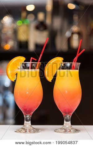 Two cocktails with orange stand on the bar counter