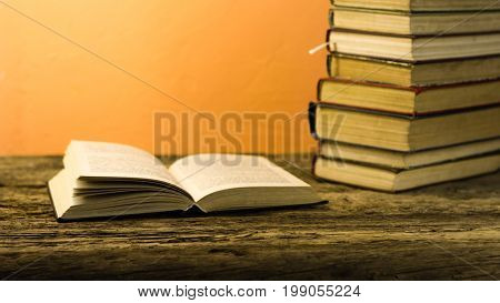Books on an old wooden table. Beautiful orange background.