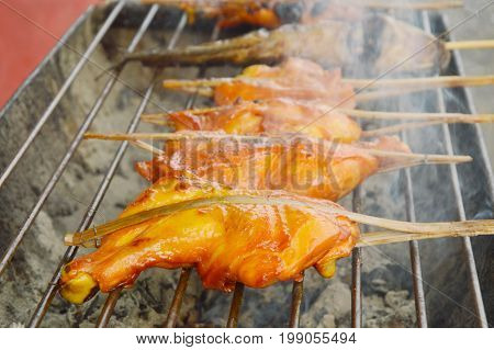 chicken grilled with smoke floating on iron stove in market