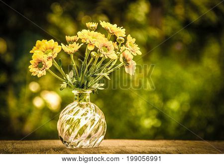A small bouquet of yellow flowers on an old wooden table. Copy space