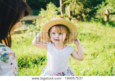 little smilling girl takes mother's hat, playing outside