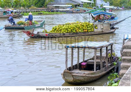 Soc Trang, Vietnam - January 21, 2017: Boats flower exchange trade on the river in the morning with the boat loaded with daisies which only sell flowers on Tet new floating market Soc Trang, Vietnam
