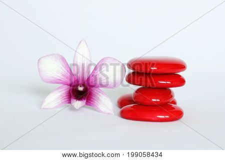 Red pebbles arranged in zen lifestyle with an orchid on the left side on a white background