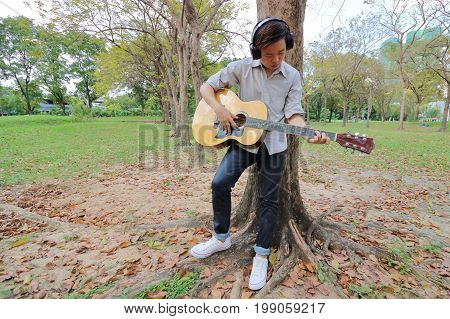 Wide angle shot. Guitarist man with headphones standing and playing acoustic guitar in outdoor park.