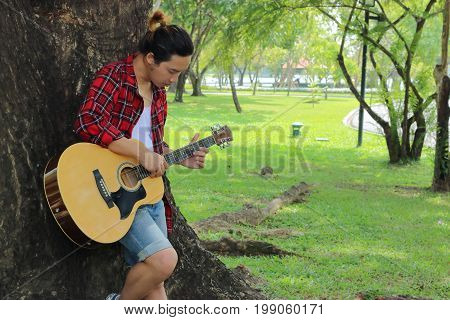 Young relaxed man is playing acoustic guitar in beautiful nature background.