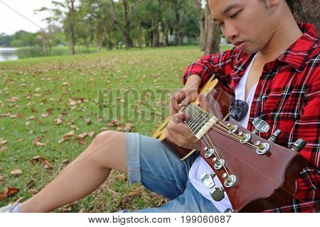 Close up young asian man in red shirt leaning against a tree and playing acoustic guitar in beautiful outdoor park. Shallow depth of field.