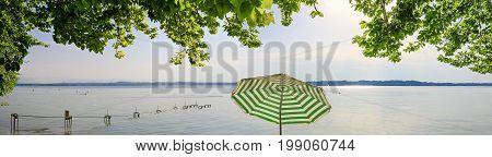 lake starnberg panorama view through green beech leaves striped sunshade
