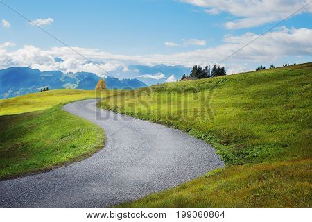 winding road over green hill in the swiss alps