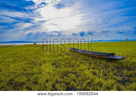 Rural river landscape summer river with bright sky and cloud. Boat in the river