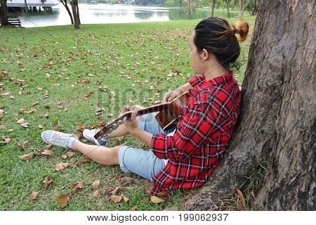 Back view of young relaxed man in red shirt leaning against a tree and playing acoustic guitar in beautiful outdoor park.