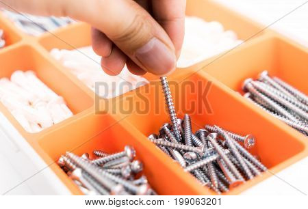 Hand picking up a screw nail from orange tool box