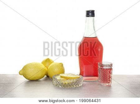 A bottle of liquor and lemons on the table closeup