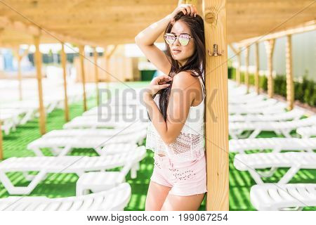 People, Fashion, Summer And Beach Concept - Happy Young Woman In Summer Clothes Over Swimming Pool A