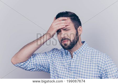 Tired Sick Young Brunet Bearded Man With Sad Grimace. He Is Holding The Forehead, Wearing The Checke