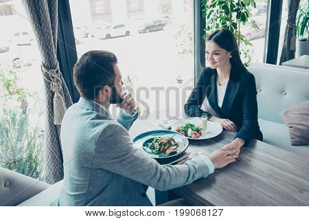 Happy Together. Two Young Cute Lovers Are Sitting In A Restaurant In A Formalwear And Hold Each Othe