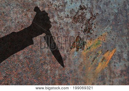 Human hand with big killing knife silhouette in shadow on rust wall background. Illustration for criminal news.