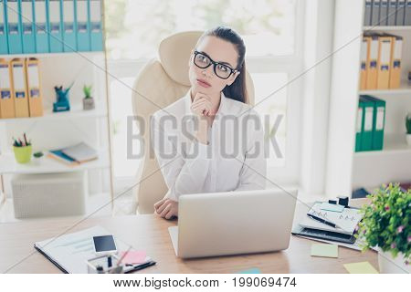 Portrait Of Serious Young Brunette Businesswoman Realtor In Formal Wear, Sitting At Her Work Place A