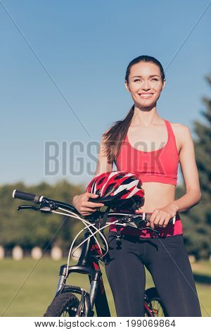 Fit Sportwoman Is Outside On A Summer Day, Finished Cicling On Modern Bike, Standing With It Proud,
