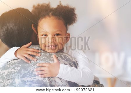 Finally back. The close up of a sweet little curly girl hugging her mother wearing a military uniform after her serving in the military for a long time and their separation for that reason