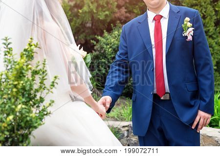 Bride and groom on their wedding day. Close-up of groom's hand holding bride's wirst tender. Wedding couple enjoying romantic moments in the garden