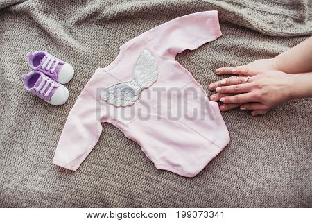 baby shirt on the sofa with shoes and moms hand beown backgriund