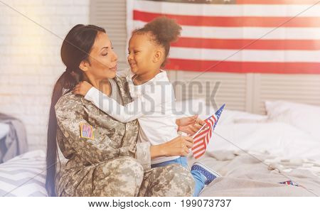 Close-knit family. Adorable little girl cuddling her mother on bed while the mother wearing a US military uniform hugging her back and holding an American flag in her hand