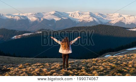 Full Length Rearview Shot Of An Adventurous Female Hiker Standing On Top Of The Mountain With Her Ar