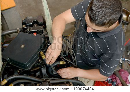 A young man mechanic repairing motor boats and other