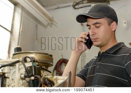 a young man mechanic repairing motor boats and phone at customer