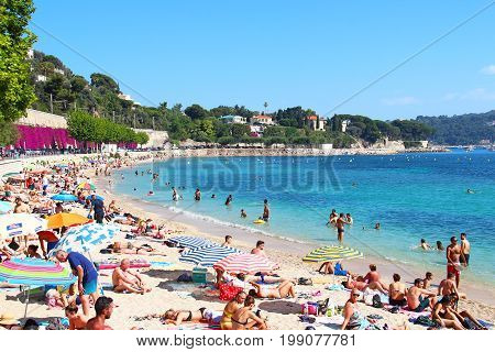 VILLEFRANCHE-SUR-MER, FRANCE - JULY 26, 2016: Crowded summer beach on Mediterranean sea near Nice, Cote d'Azur, French riviera