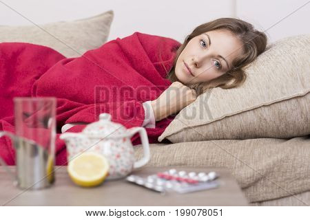 Sick woman covered with a blanket lying in bed with high fever and a flu. Pills teapot and lemon on the table