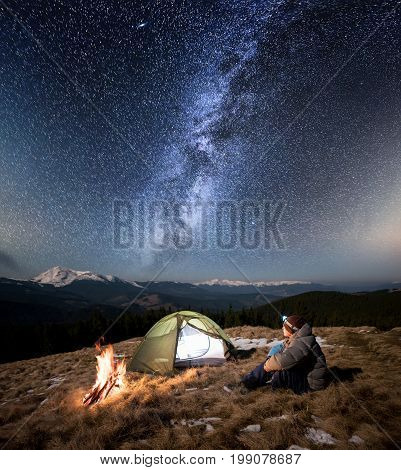 Male Tourist Have A Rest In His Camp At Night. Man With A Headlamp Sitting Near Campfire And Tent Un