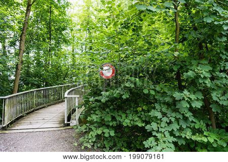 do not pass stop sign in front of a bridge overgrown by trees