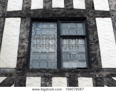 leaded glass window in a half timbered medieval type building with black oak beams and white plaster walls