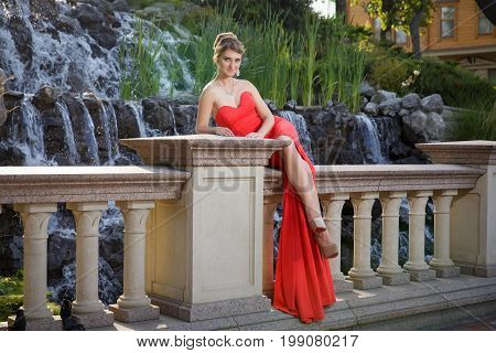 Young girl in red dress exploring beautiful waterfall at the sunset time during her luxury travel wanderlust globetrotter