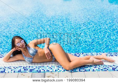 Woman In Blue Bikini Lying At The Edge Of Swimming Pool