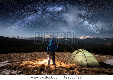 Female Tourist Enjoying In Her Camp At Night. Woman Standing Near Campfire And Green Tent Under Beau