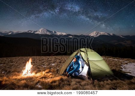 Female Tourist Enjoying In Her Camp At Night. Woman Sitting Near Campfire And Green Tent Under Beaut