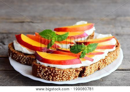 Easy sandwiches with cream cheese, fresh nectarines and mint on a plate isolated on vintage wooden table. Cream cheese and fruit sandwich idea. Rustic style. Closeup