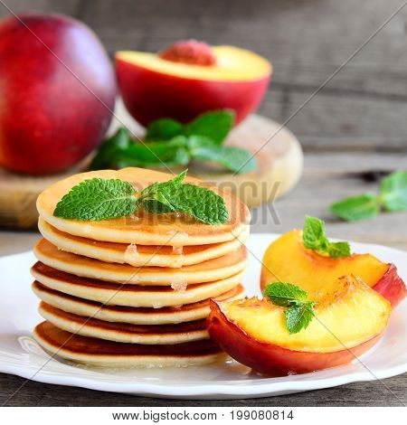 Yummy pancakes with sirup, nectarine and mint on a plate. Easy pancakes recipe for kids. Rustic style. Closeup