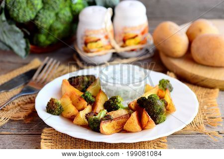 Roasted vegetables idea. Roasted potatoes slices and broccoli with sauce on a white plate and a wooden table. Fork, knife, salt and pepper shaker on a vintage wooden background. Closeup