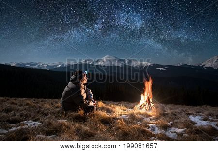 Male Tourist Have A Rest In The Mountains At Night. Man With A Headlamp Sitting Near Campfire Under