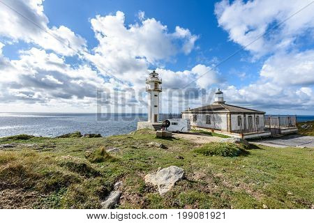 CABO TOURINAN SPAIN - MAY 17 2017: Tourists with RV motorhome camper at Cabo Tourinan - the most western point of Spain with lighthouse. Popular tourist and pilgrim destination. Beautiful old lighthouse on rocky cliff and Atlantic ocean in Spain.