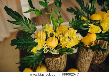 Bouquet of flowers on wooden background selective focus Delicate composition with flowers and fruits. Lemon composition wedding.