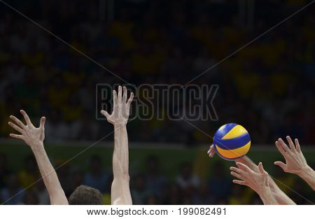 Hand and ball on the block in a volley match with dark background