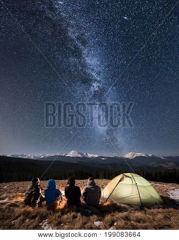 Rear View Of Four People Sitting Together Beside Camp And Tent Under Beautiful Night Sky Full Of Sta