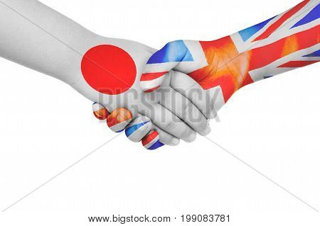 Handshake between Japan and United Kingdom with flags painted on child's hands in isolated white background