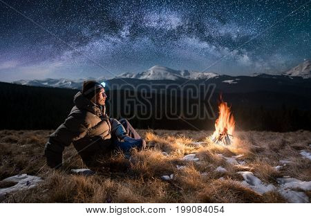 Male Tourist Have A Rest In The Mountains At Night. Guy With A Headlamp Sitting Near Campfire Under
