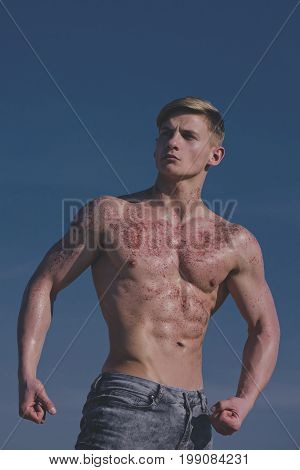 Adam with glitter on bare chest. Athletic bodybuilder pose as hercules. Gladiator or atlant. Sport and workout. Man with muscular wet body.