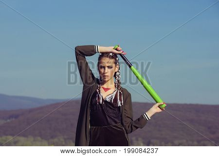 Sport or criminal girl outdoor. Beauty and fashion. Hooligan on blue sky. Bandit gang and conflict. Woman with baseball bat.